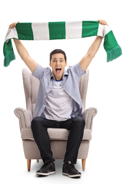 Excited sports fan sitting in an armchair and holding a scarf stock photo