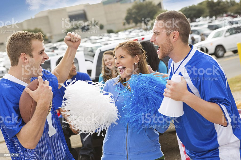 Excited sports fans celebrating outside college stadium royalty-free stock photo