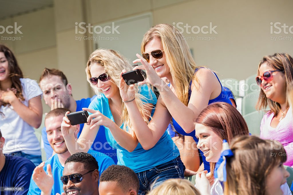 Excited sports fans taking photos during sporting event in stadium stock photo