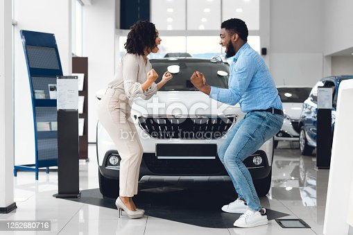 New Car. Excited Black Spouses Celebrating Shaking Fists Standing Near New Family Auto In Automobile Dealership Store
