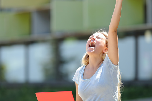 istock Excited student celebrating success outdoors 1169370273