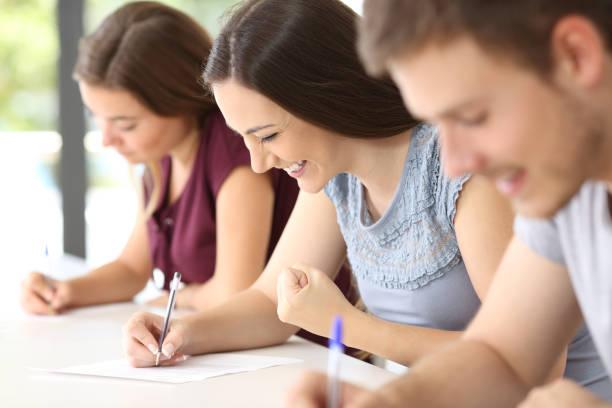 animado estudante durante um exame em sala de aula - happy test results - fotografias e filmes do acervo
