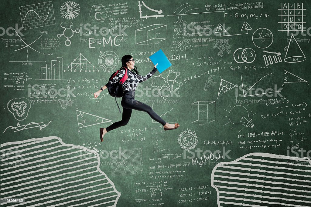 Excited student jumping on gap stock photo