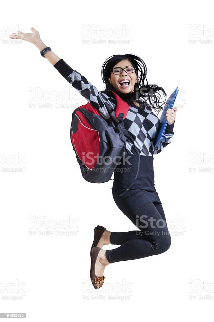 Excited student jumping on white background stock photo