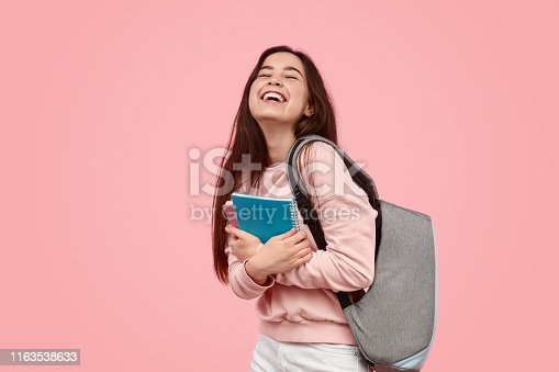 Cheerful teen girl with backpack embracing notepads and laughing while standing against pink background during studies