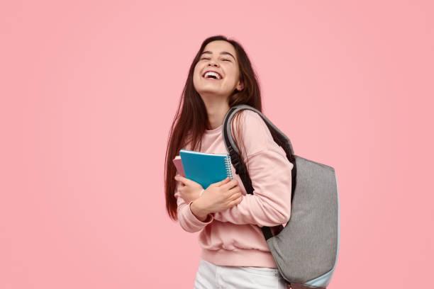 aufgeregter student lacht und umarmt notizbücher - jugendalter stock-fotos und bilder
