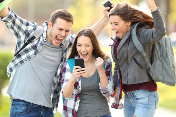 Excited students checking exam grades online stock photo