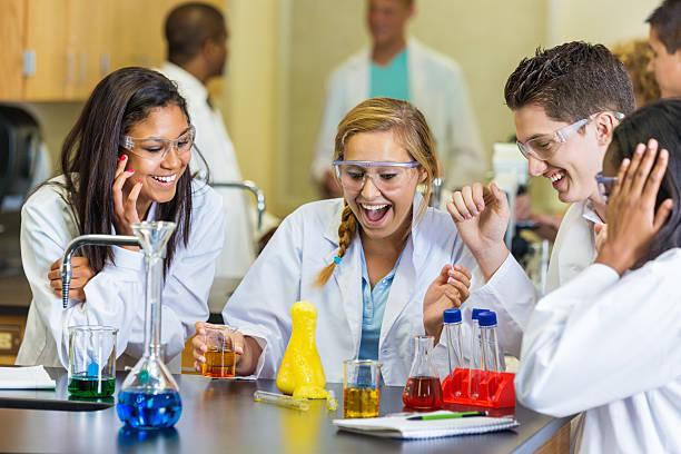 glücklich studenten, die wissenschaft experimentieren in high school class - versuche nicht zu lachen stock-fotos und bilder