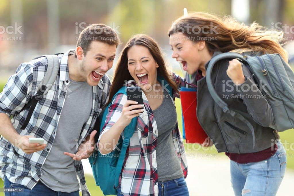 Animado estudantes recebendo boas notícias no telefone - foto de acervo
