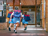 Rear view of excited students running towards entrance. Girls are carrying backpacks while leaving from school. Happy friends are wearing school uniforms.