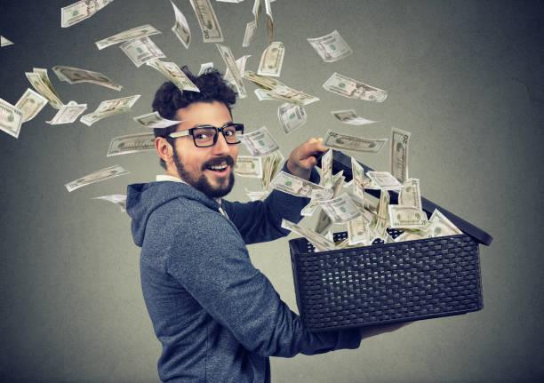 興奮して成功するビジネス人を飛んでお金でボックスを開く - 柱頭 ストックフォトと画像