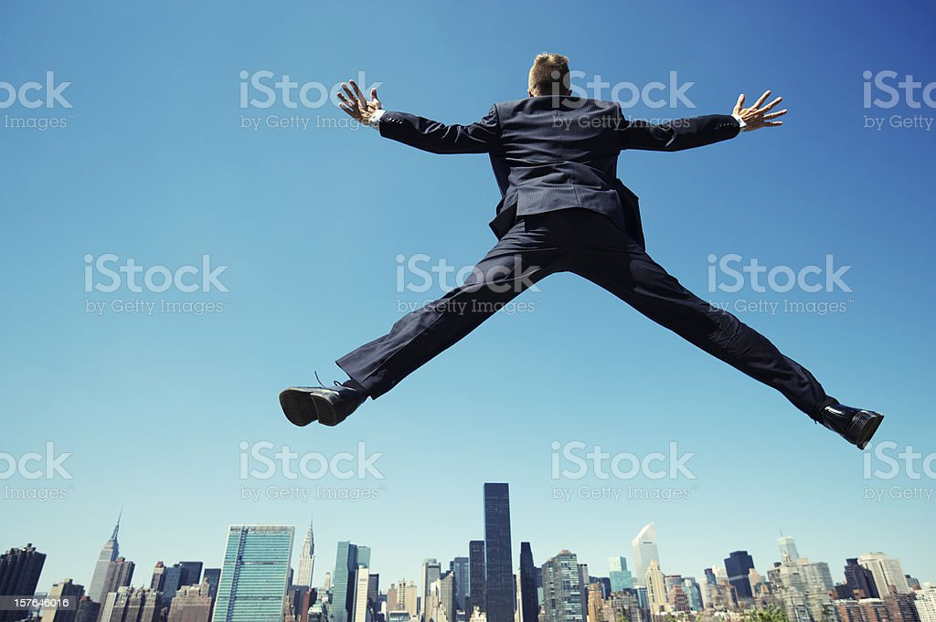 Excited Successful Businessman Jumping Over City Skyline stock photo
