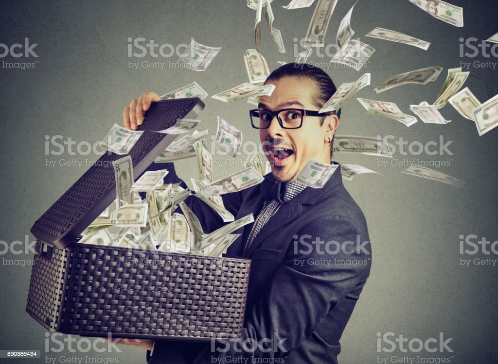 Excited successful man opening a box with money flying out away – zdjęcie