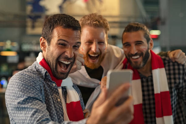 Excited supporters watching football match on phone Excited men watching football in streaming on smartphone in bar. Football fans watching game on smart phone and celebrating victory score at pub. Happy supporters cheering and exulting after winning an online bet. football fans stock pictures, royalty-free photos & images