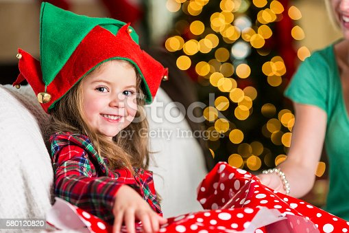 579124316 istock photo Excited sweet girl opens gift on Christmas morning 580120820