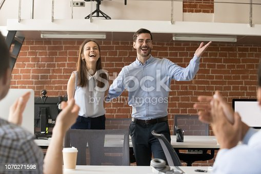 istock Excited team leader congratulating employee with promotion while team applauding 1070271598
