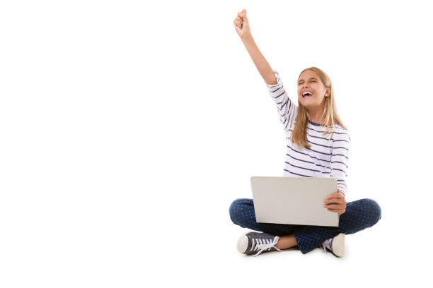 âexcited teen girl sitting on the floor, celebrating success with arm raised,isolated - excited emoji stock photos and pictures