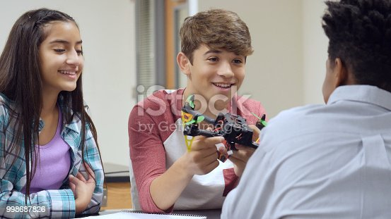 istock Excited teenage boy shows off robotics lab project 998687826