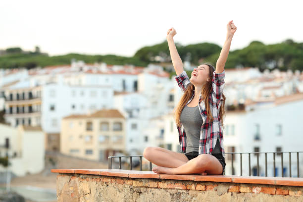 Excited teenage girl celebrating new day on a ledge stock photo