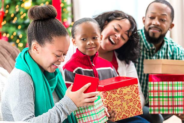 excited teenage girl opens christmas gift - geschenke eltern weihnachten stock-fotos und bilder