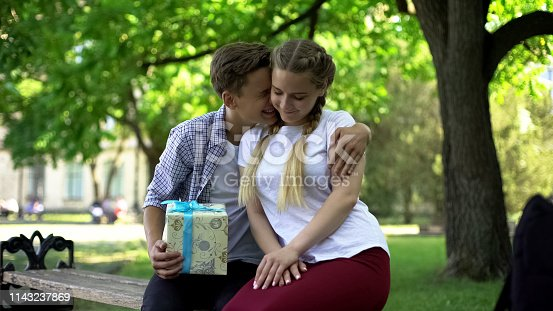 istock Excited teenager with gift box embracing girlfriend, happy to get present, b-day 1143237869