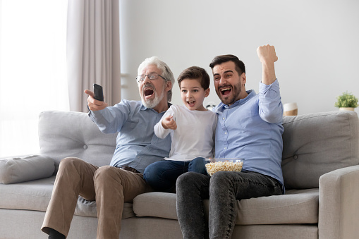 Excited three generation men family watch tv sport game