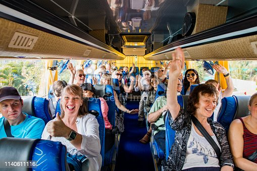 A front-view shot of a large multi-ethnic group of tourists celebrating on a coach bus, they are smiling and raising their arms with excitement, they are ready to begin their journey.