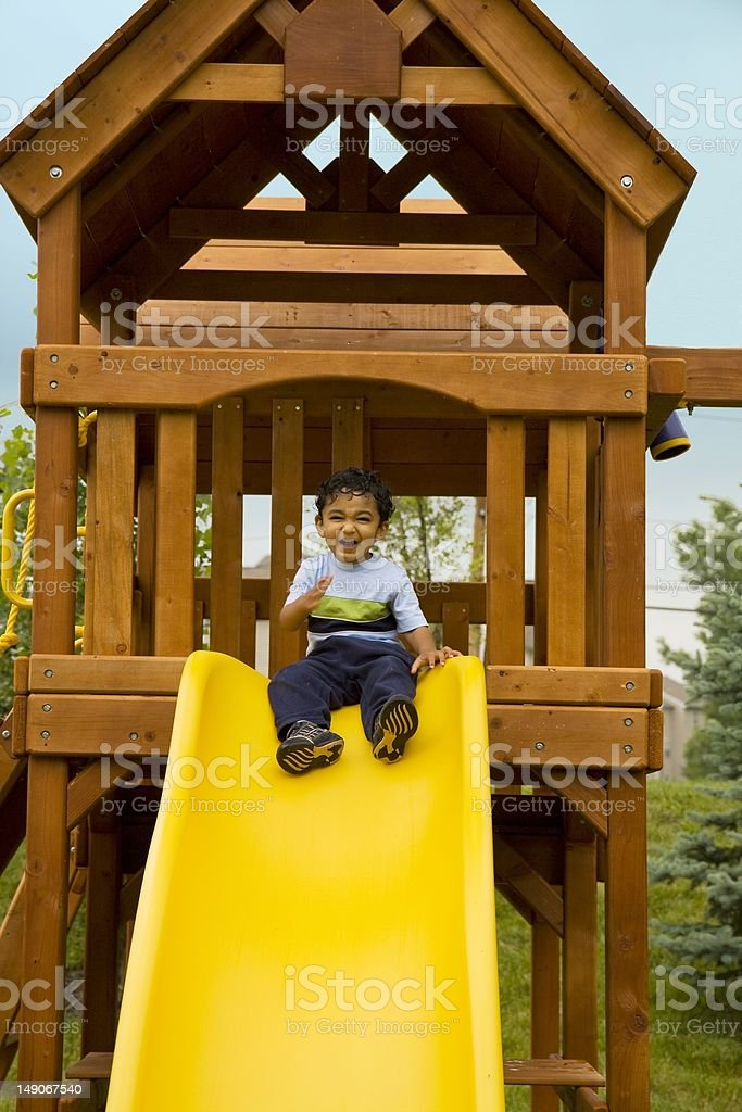 Excited Toddler Sitting in a Tree-House Ready to Slide stock photo