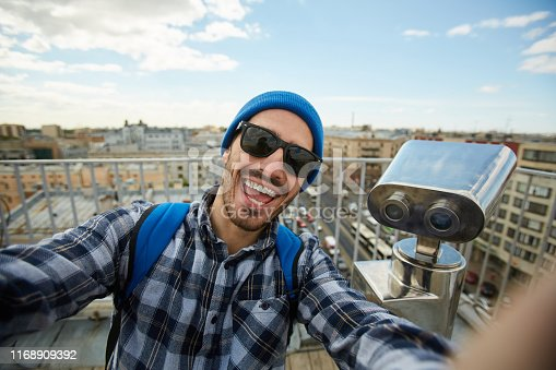 Portrait of excited tourist posing for selfie photo standing at rooftop viewing platform, copy space