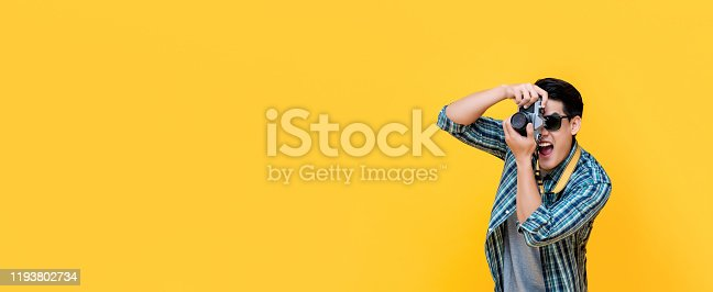 Excited Asian tourist photographer taking photo with camera on yellow banner background with copy spacce