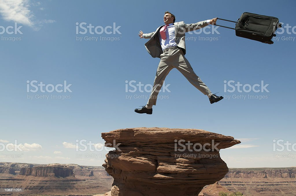 Excited Traveling Businessman Jumping Outdoors on Mesa Rock stock photo