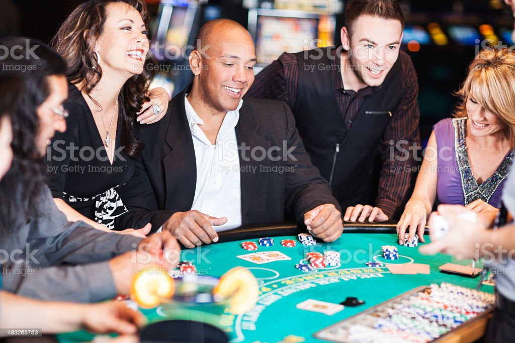 Excited winner at the blackjack table surrounded by happy friends stock photo
