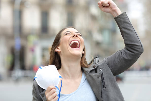 Excited woman celebrating holding mask on city street stock photo