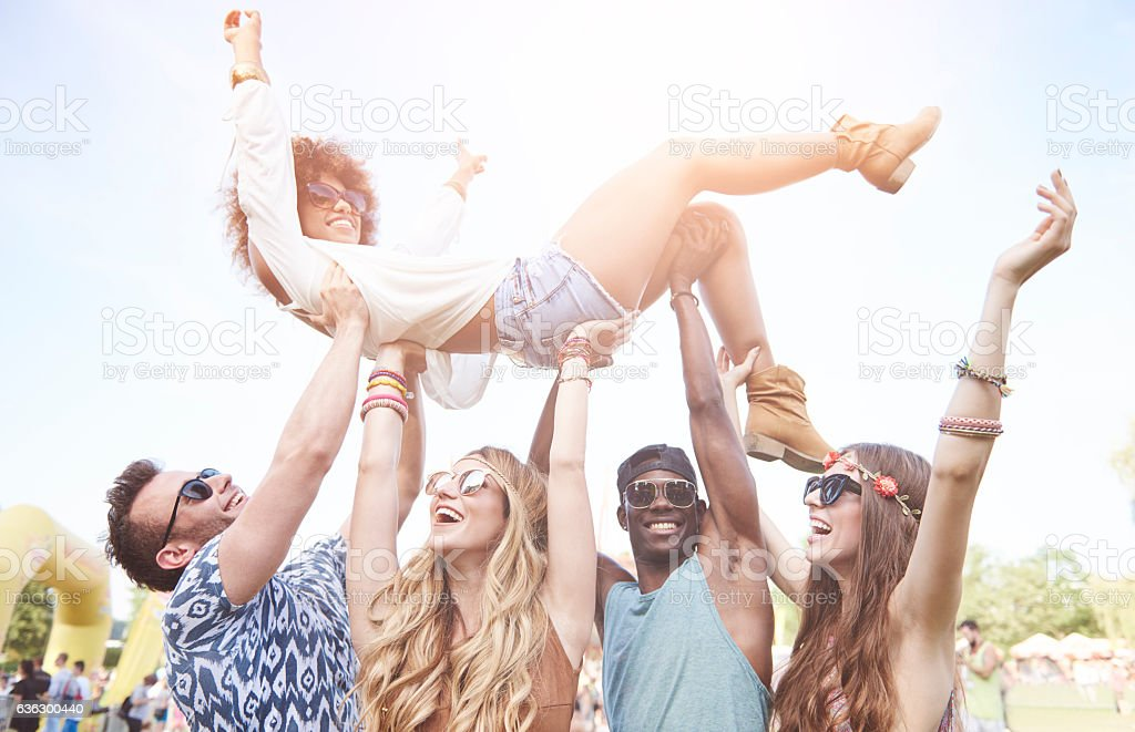 Excited woman crowd surfing at music festival stock photo