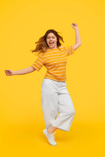 Excited woman dancing with closed eyes stock photo