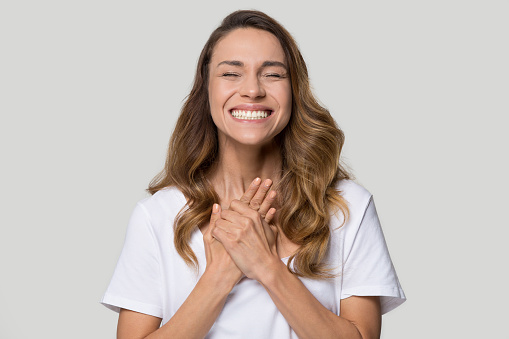 Head shot studio portrait young emotional woman closed eyes holding arms on chest feels happiness and gratitude come from heart, gesture express sincere heartfelt appreciation and gratefulness concept