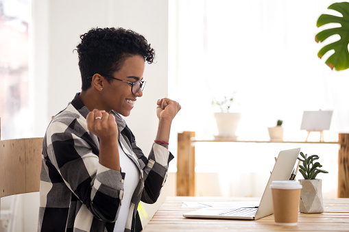 istock Excited woman feels happy sitting at the desk indoors 1156082367
