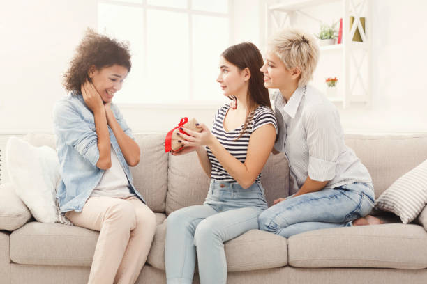 Excited woman getting gift from her friends Happy girls exchanging gifts. Excited woman getting present from her friends. Birthday, holidays, celebration and female friendship concept, copy space group of friends giving gifts to the birthday girl stock pictures, royalty-free photos & images