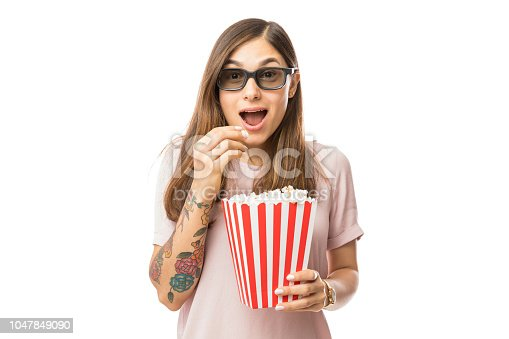 istock Excited Woman Having Popcorn While Watching 3D Movie 1047849090