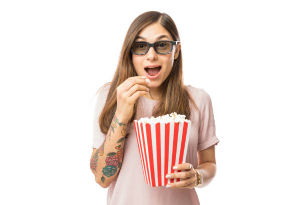 Excited Woman Having Popcorn While Watching 3D Movie Excited woman having popcorn while watching 3D movie over white background 3 d glasses stock pictures, royalty-free photos & images