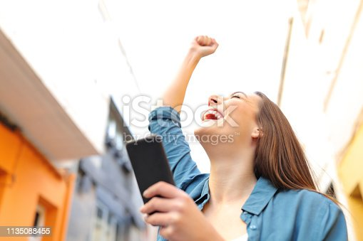 istock Excited woman holding smart phone celebrates success 1135088455
