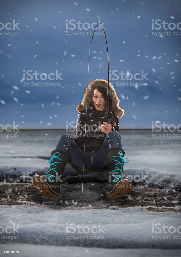 Excited woman ice fishing on the bay stock photo