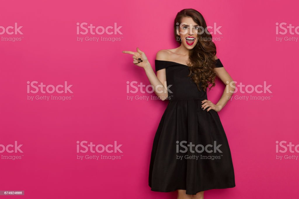 Excited Woman In Elegant Black Dress Is Pointing royalty-free stock photo