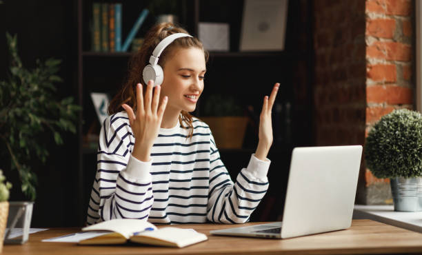 excited woman in headphones having conversation on video chat while using laptop at home - remote work imagens e fotografias de stock