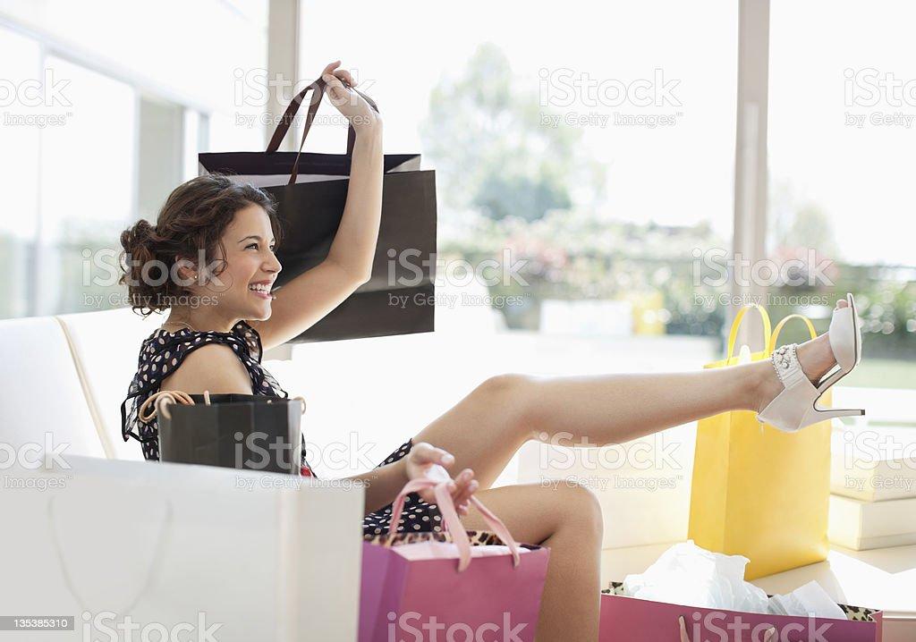 Prazer mulher na sala de estar com sacos de Compras - fotografia de stock