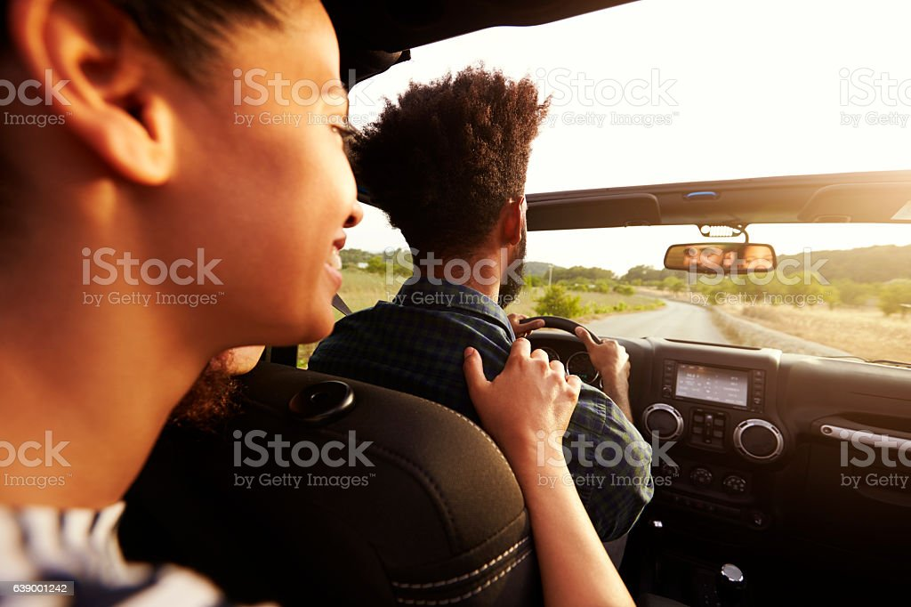 Excited woman in the back of car, hand on shoulder stock photo