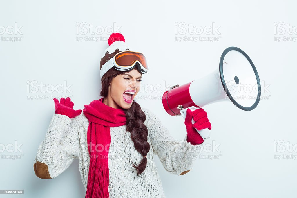 Excited woman in winter outfit, shouting into megaphone stock photo