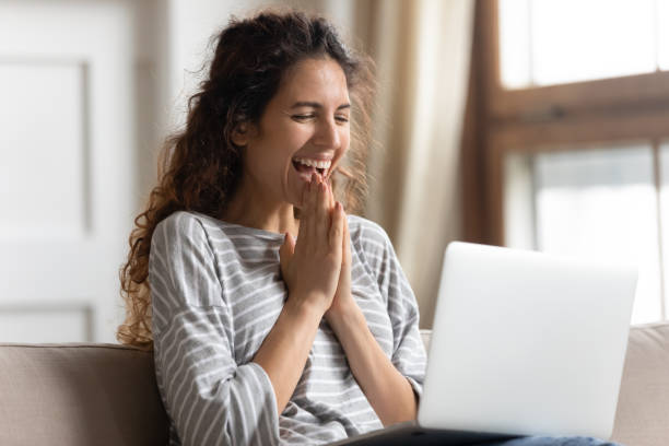Excited woman looking at laptop screen, rejoicing good news stock photo