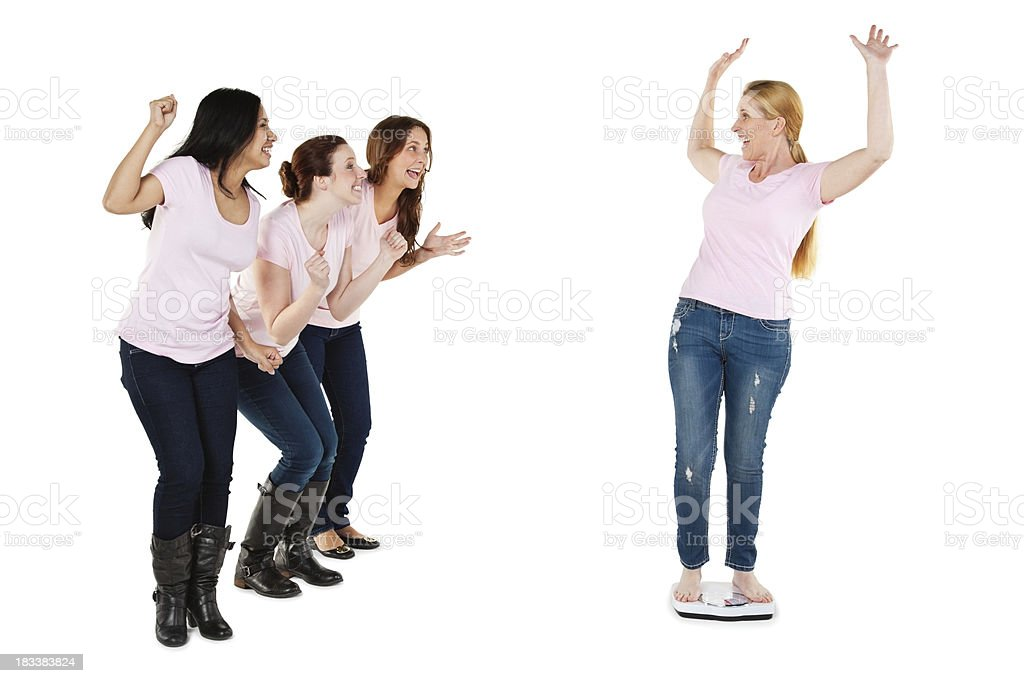 Excited Woman on Scale Being Encouraged By Her Friends royalty-free stock photo