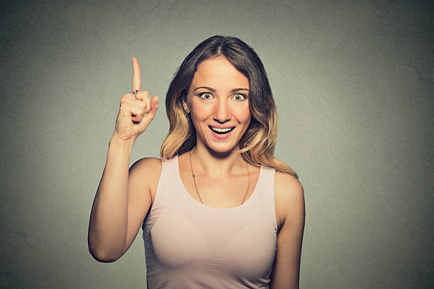 excited woman pointing with finger up Portrait happy beautiful excited woman pointing with finger up isolated on grey wall background. Positive human face expressions, emotions, feelings body language, perception aha stock pictures, royalty-free photos & images